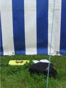 Rucksack, seat pad and sunglasses on the grass behind the marquee.