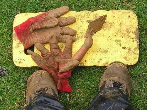 Muddy gloves, boots and trowel