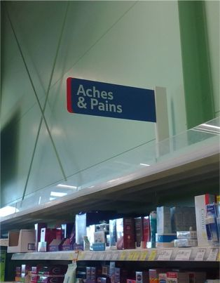Sign over shelves in Tesco announcing 'Aches and Pains'