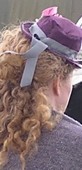 Lady wearing ribboned purple hat over long curly hair