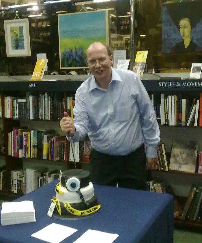 Richard Reynolds cutting cake with Crime Scene tape icing