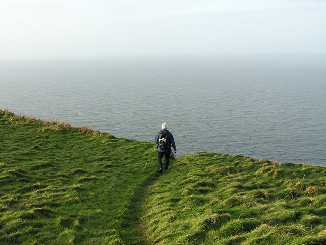 View of walker looking out from clifftop across hazy sea
