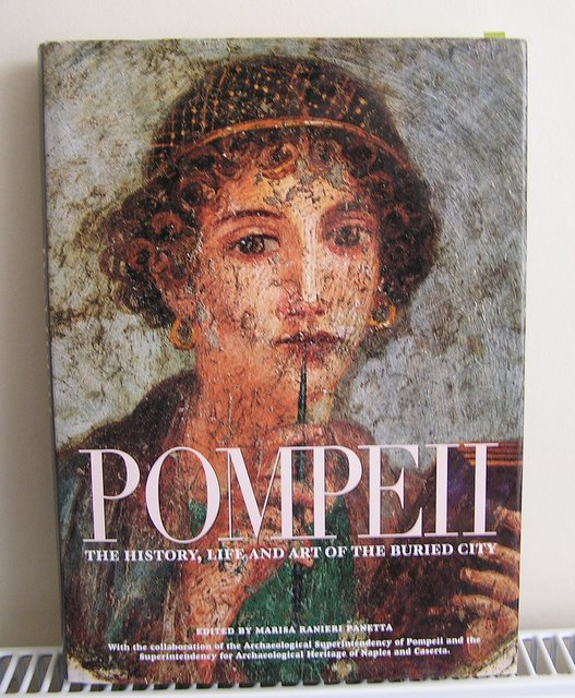 Cover of book called POMPEII showing portrait of woman with writing materials