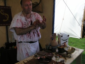 Photo of Roman re-enactor in bloodstained tunic explaining medical instruments