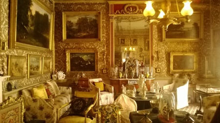 Room crammed with gold-framed paintings and elegant furniture