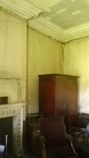 Room with spartan furnishings and damp peeling wallpaper