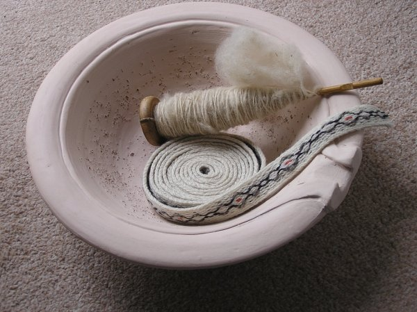 Picture of dish with gritted surface, woolen braid and spindle