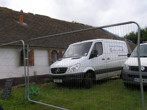 Builders' vans outside villa