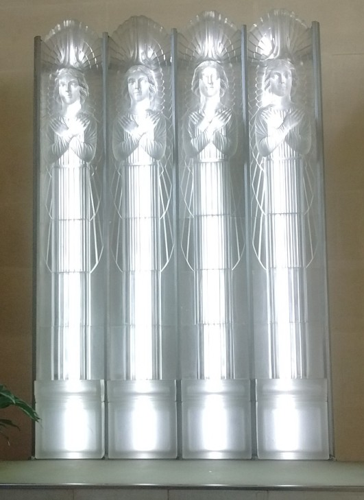 Angels depicted in glass with lights behind them