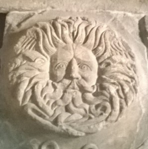 Carving of moustachioed face on temple pediment at Bath