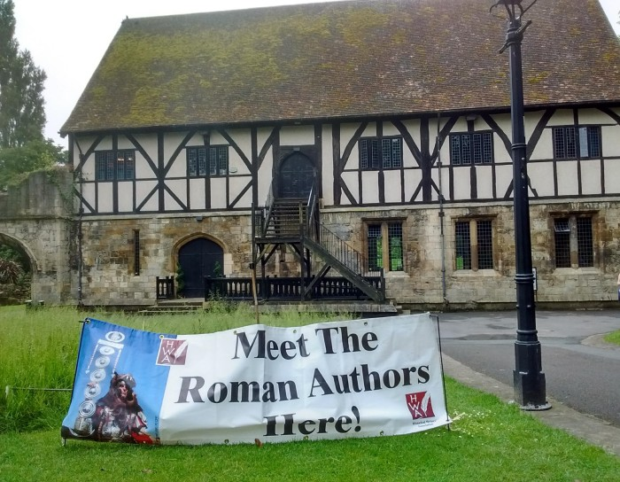 "Sign saying ""Meet the Roman authors here"" outside half-timbered building"