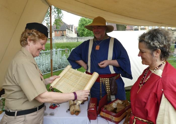 Re-enactor showing a handwritten scroll to two women.