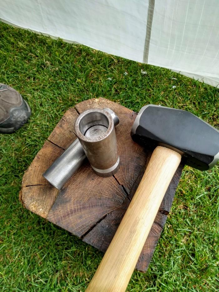 Engraved die set up on wooden block. Hammer.