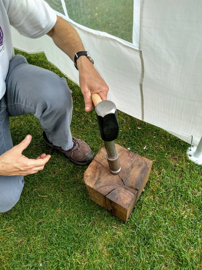 Hand holding hammer and hitting the top of the second die.