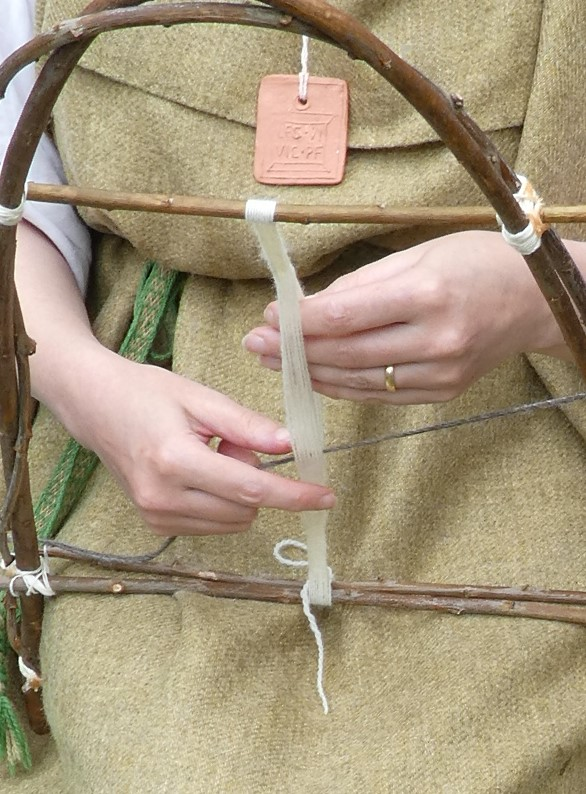 Weaving by hand-twisting strands held taut on a loom made of bent twigs.