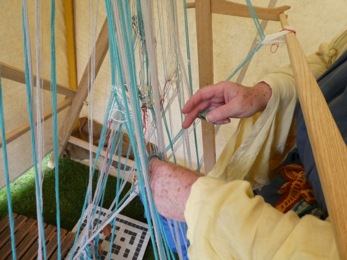 Weaver setting up strands of wool on a wooden loom.